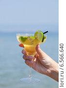 Купить «Женская рука держит стеклянный бокал с коктейлем на фоне моря», фото № 6566640, снято 14 августа 2014 г. (c) Данил Руденко / Фотобанк Лори