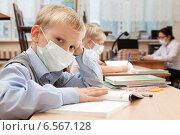 Купить «Мальчик в медицинской одноразовой маске за партой в школе», фото № 6567128, снято 20 октября 2014 г. (c) Владимир Мельников / Фотобанк Лори