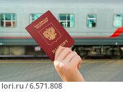 Купить «Российский паспорт в руке на фоне железнодорожного вагона. Электронный билет на поезд», эксклюзивное фото № 6571808, снято 13 сентября 2014 г. (c) Володина Ольга / Фотобанк Лори