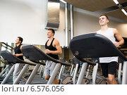 Купить «smiling men exercising on treadmill in gym», фото № 6576056, снято 28 сентября 2014 г. (c) Syda Productions / Фотобанк Лори
