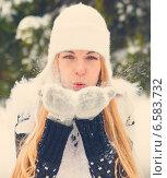 Красивая блондинка дует на снег на варежках на зимней улице. Стоковое фото, фотограф Дарья Петренко / Фотобанк Лори