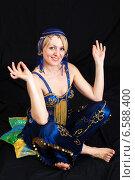 Купить «Улыбающаяся молодая женщина сидит, сложив ноги по-турецки», фото № 6588400, снято 12 марта 2014 г. (c) Сергей Дубров / Фотобанк Лори