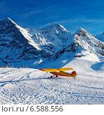 Желтый самолет в горах Швейцарии зимой (2013 год). Стоковое фото, фотограф Роман Бабакин / Фотобанк Лори