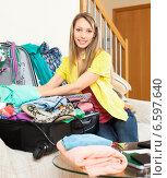 Купить «smiling woman packs suitcase», фото № 6597640, снято 21 апреля 2014 г. (c) Яков Филимонов / Фотобанк Лори
