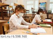 Купить «Школьницы в медицинских защитных масках за партой в пустом школьном классе», фото № 6598160, снято 21 октября 2018 г. (c) Владимир Мельников / Фотобанк Лори