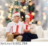 Купить «happy senior couple in santa hats with gift boxes», фото № 6602784, снято 21 августа 2014 г. (c) Syda Productions / Фотобанк Лори