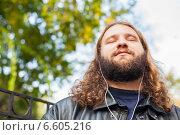 Длинноволосый бородатый мужчина слушает музыку в парке (2014 год). Стоковое фото, фотограф Ilie-Cristian IONESCU / Фотобанк Лори