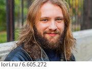 Молодой длинноволосый мужчина с бородой в черной куртке слушает музыку в наушниках (2014 год). Стоковое фото, фотограф Ilie-Cristian IONESCU / Фотобанк Лори