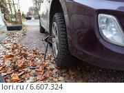 Купить «Переднее колесо автомобиля на домкрате во время замены летней резины на зимнюю», фото № 6607324, снято 25 октября 2014 г. (c) Кекяляйнен Андрей / Фотобанк Лори