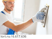 Купить «smiling builder with grinding tool indoors», фото № 6617636, снято 25 сентября 2014 г. (c) Syda Productions / Фотобанк Лори