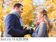 smiling couple with coffee cups in autumn park. Стоковое фото, фотограф Syda Productions / Фотобанк Лори
