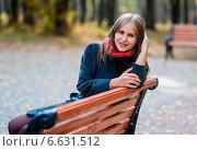 Купить «Весёлая девушка сидит на скамейке в осеннем парке», эксклюзивное фото № 6631512, снято 13 октября 2014 г. (c) Игорь Низов / Фотобанк Лори
