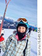 Девочка с лыжами в горнолыжном снаряжении на фоне гор. Стоковое фото, фотограф Максим Топчий / Фотобанк Лори