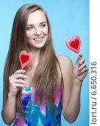 Красивая молодая женщина с леденцами на палочке в виде сердца. Стоковое фото, фотограф Nikolay Safronov / Фотобанк Лори