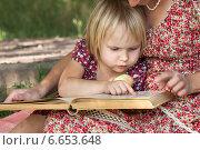 Маленькая девочка смотрит в книгу, которую читает её мама. Стоковое фото, фотограф Мороз Елена / Фотобанк Лори