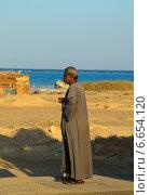 Мужчина-араб с сигаретой на фоне моря и песка (2014 год). Редакционное фото, фотограф Марина Зубрицкая / Фотобанк Лори