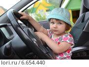 Милая маленькая девочка сидит за рулем автомобиля. Стоковое фото, фотограф Абызова Елена / Фотобанк Лори