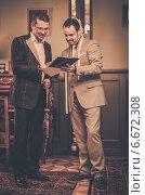 Купить «Tailor and client choosing cloth and buttons for custom made suit», фото № 6672308, снято 12 ноября 2014 г. (c) Andrejs Pidjass / Фотобанк Лори