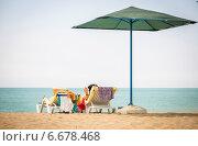 Пара на берегу средиземного моря отдыхает на шезлонгах. Стоковое фото, фотограф Елена Мартынова / Фотобанк Лори