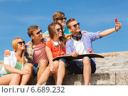 Купить «group of smiling friends with smartphone outdoors», фото № 6689232, снято 10 августа 2014 г. (c) Syda Productions / Фотобанк Лори