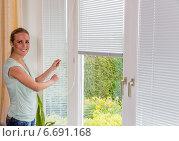 woman lets down blinds. Стоковое фото, фотограф Erwin Wodicka / Фотобанк Лори