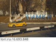 Жёлтый автомобиль такси едет по улице Маяковской в Старых Химках, Подмосковье (2014 год). Редакционное фото, фотограф Тамара Заводскова / Фотобанк Лори