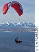 Купить «Полет на параплане над водой на фоне гор», фото № 6699564, снято 21 ноября 2014 г. (c) А. А. Пирагис / Фотобанк Лори