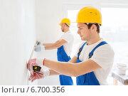 Купить «group of builders with measuring tape indoors», фото № 6700356, снято 25 сентября 2014 г. (c) Syda Productions / Фотобанк Лори