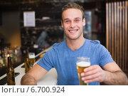 Купить «Young man holding pint of beer», фото № 6700924, снято 27 июня 2014 г. (c) Wavebreak Media / Фотобанк Лори
