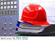 Купить «Строительная каска на чертежах папках с документацией», фото № 6701552, снято 25 мая 2014 г. (c) yeti / Фотобанк Лори