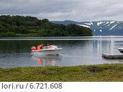 Купить «Катер с туристами отплывает от берега на Курильском озере на Камчатке на фоне сурового горного пейзажа», эксклюзивное фото № 6721608, снято 29 июля 2014 г. (c) Ольга Липунова / Фотобанк Лори