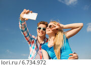 Купить «smiling couple with smartphone making selfie», фото № 6734972, снято 7 июля 2014 г. (c) Syda Productions / Фотобанк Лори