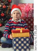 Счастливый мальчик в новогоднем колпаке с подарками возле елки. Стоковое фото, фотограф Сергей Богданов / Фотобанк Лори