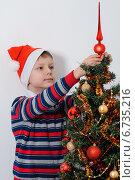 Мальчик в новогоднем колпаке украшает елку. Стоковое фото, фотограф Сергей Богданов / Фотобанк Лори