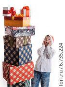 Удивленный мальчик смотрит на гору новогодних подарков. Стоковое фото, фотограф Сергей Богданов / Фотобанк Лори