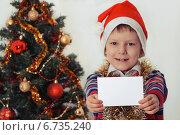 Счастливый мальчик в новогоднем колпаке возле елки держит поздравительную карточку. Стоковое фото, фотограф Сергей Богданов / Фотобанк Лори