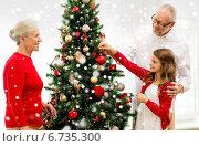 Купить «smiling family decorating christmas tree at home», фото № 6735300, снято 14 сентября 2014 г. (c) Syda Productions / Фотобанк Лори