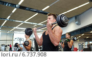Купить «group of men flexing muscles with barbell in gym», фото № 6737908, снято 28 сентября 2014 г. (c) Syda Productions / Фотобанк Лори