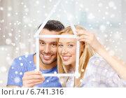 Купить «smiling couple holding house model at home», фото № 6741316, снято 9 февраля 2014 г. (c) Syda Productions / Фотобанк Лори