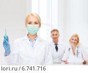 Купить «doctor in mask holding syringe with injection», фото № 6741716, снято 15 апреля 2014 г. (c) Syda Productions / Фотобанк Лори