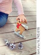 Маленькая девочка играет с деревянным рождественским оленем и еловыми шишками. Стоковое фото, фотограф Светлана Витковская / Фотобанк Лори