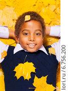 Купить «Улыбающийся темнокожий мальчик лежит на осенних листьях», фото № 6756200, снято 19 октября 2014 г. (c) Сергей Новиков / Фотобанк Лори