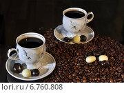Купить «Чашки и зёрна кофе с конфетами на тёмном фоне», фото № 6760808, снято 30 ноября 2014 г. (c) Сергей Галинский / Фотобанк Лори
