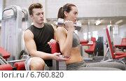 Купить «young couple with dumbbell flexing muscles in gym», видеоролик № 6760820, снято 1 декабря 2014 г. (c) Syda Productions / Фотобанк Лори