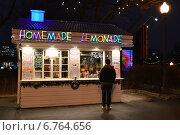 Купить «Молодой человек стоит у витрины торговой палатки в парке Горького в Москве ночью», эксклюзивное фото № 6764656, снято 5 декабря 2014 г. (c) lana1501 / Фотобанк Лори
