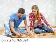 Купить «smiling couple measuring wood flooring», фото № 6765324, снято 26 января 2014 г. (c) Syda Productions / Фотобанк Лори