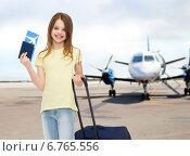 Купить «smiling girl with travel bag ticket and passport», фото № 6765556, снято 30 апреля 2014 г. (c) Syda Productions / Фотобанк Лори