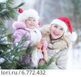 Счастливая мать и ребенок в колпаках Санты на открытом воздухе. Стоковое фото, фотограф Андрей Кузьмин / Фотобанк Лори