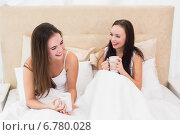 Купить «Pretty friends having coffee in bed», фото № 6780028, снято 20 июня 2014 г. (c) Wavebreak Media / Фотобанк Лори