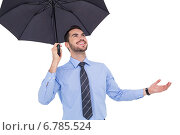 Купить «Happy businessman sheltering with a black umbrella», фото № 6785524, снято 25 июня 2014 г. (c) Wavebreak Media / Фотобанк Лори